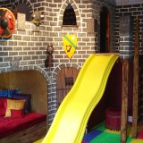 Castle playroom design with yellow slide.