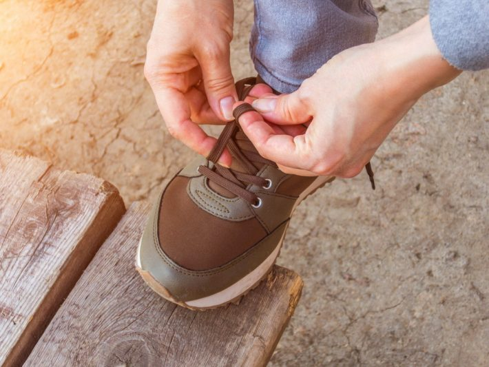 Girl tying shoelaces on sneakers, put his foot on a wooden bench in the Park