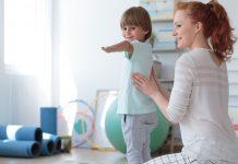 Gimnastyka korekcyjna - fizjoterapeutka ćwicząca z dzieckiem.